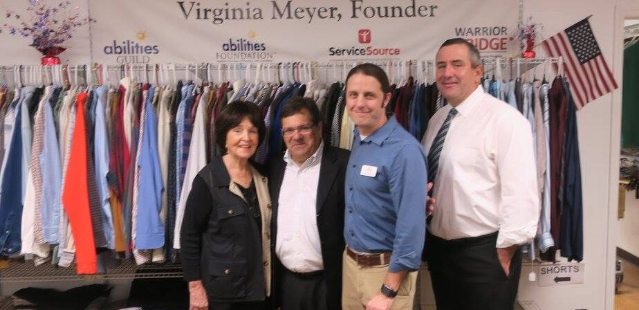 group smiling at camera in front of clothing rack