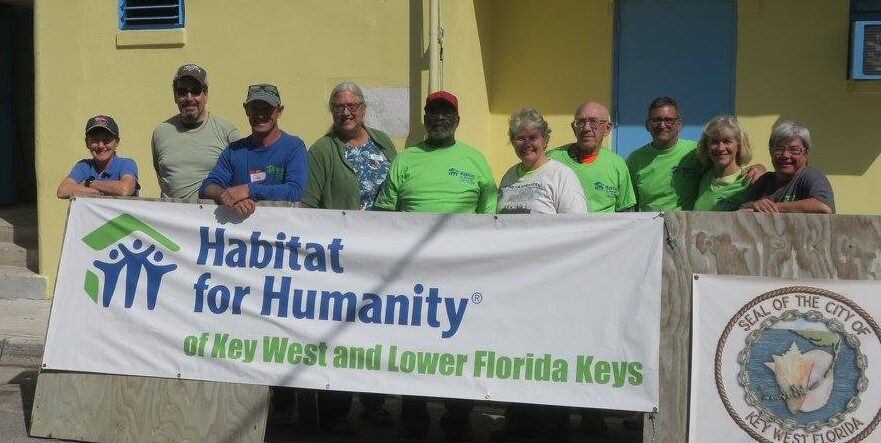 group of people standing in front of sign for Habitat for Humanity