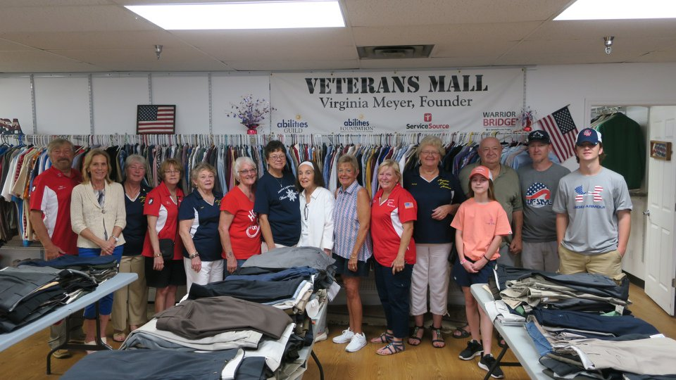large group of people standing in front of clothing rack