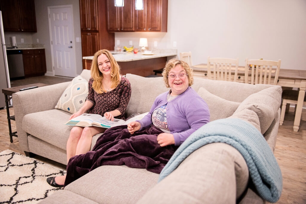 Two women sitting on a couch, smiling at the camera