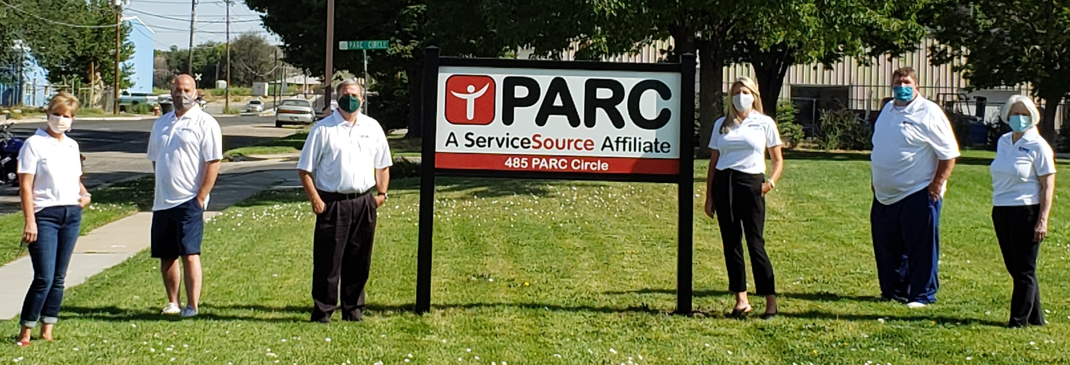 Group of people standing outside in front of sign that says PARC ServiceSource affiliate