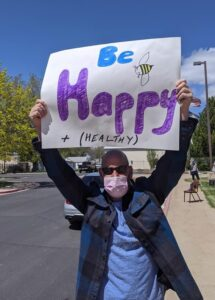 man with mask on holding a sign that says be happy and healthy