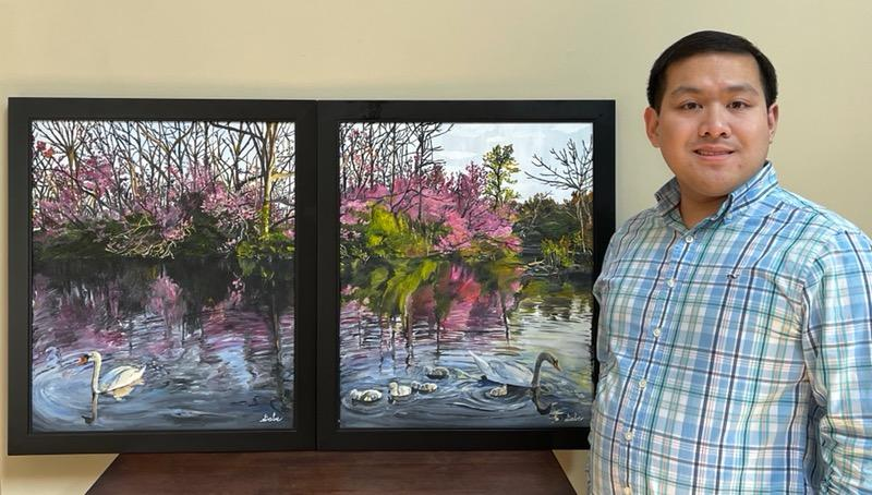 man poses next to colorful artwork on black canvas