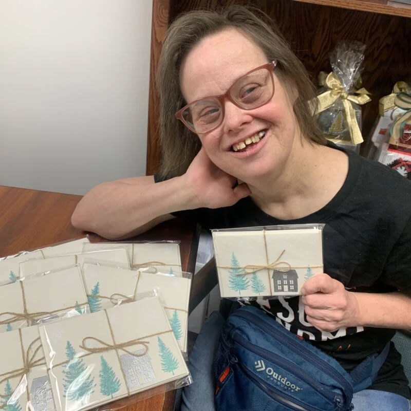 Woman holds package of greeting cards she created for sale