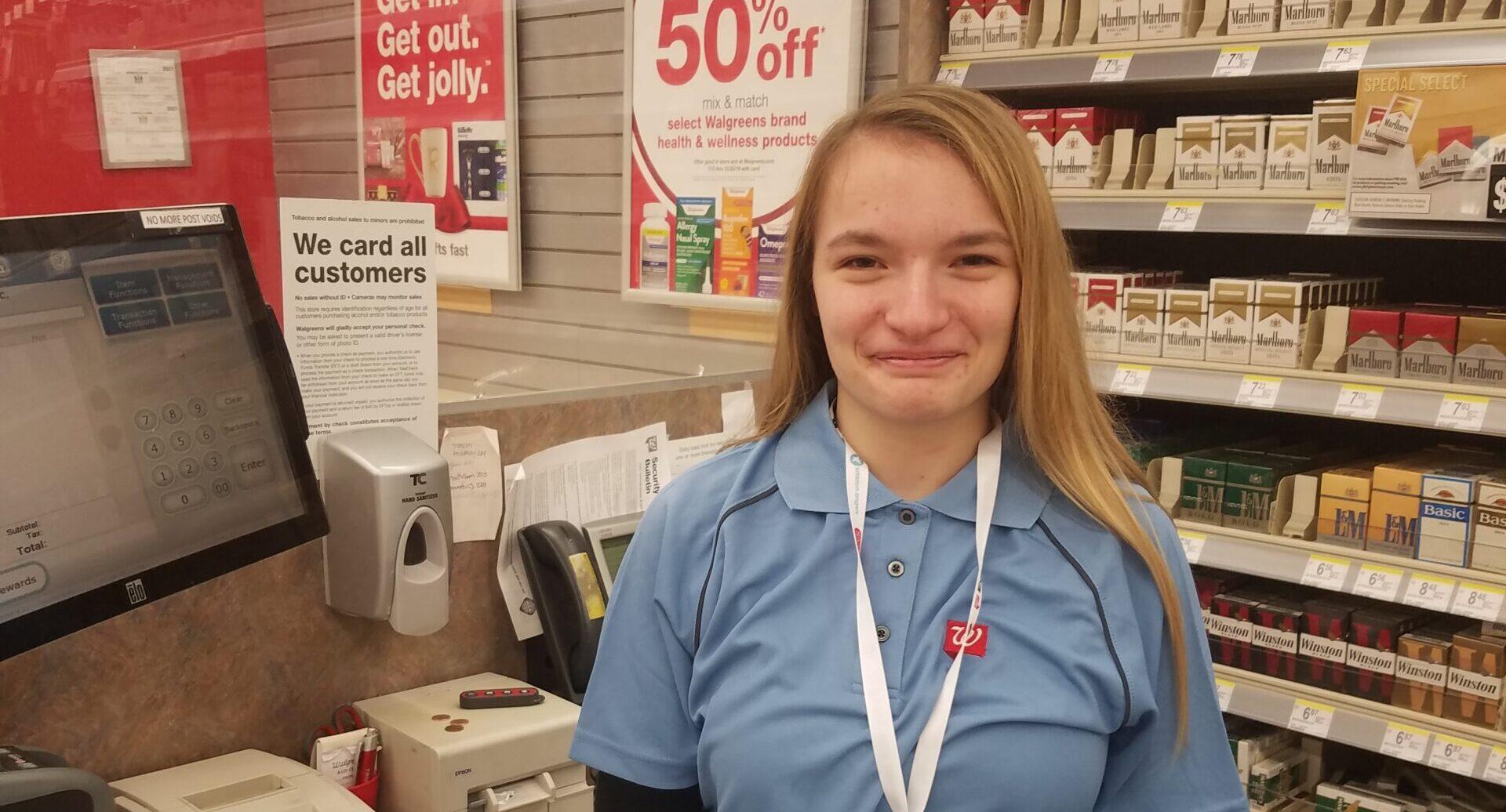 person smiling at camera behind cash register at Walgreens