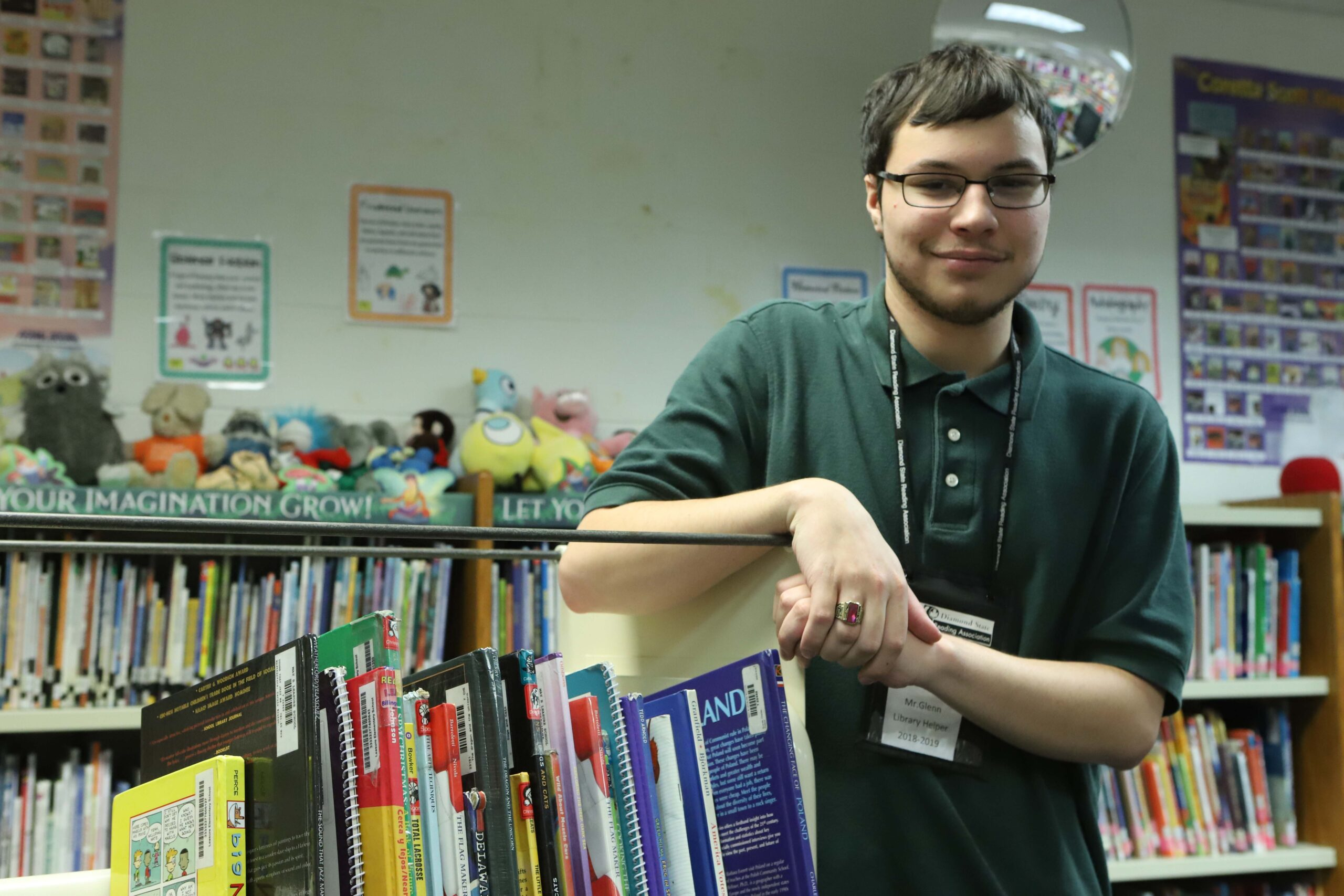 man leaning on shelf of books smiling at camera