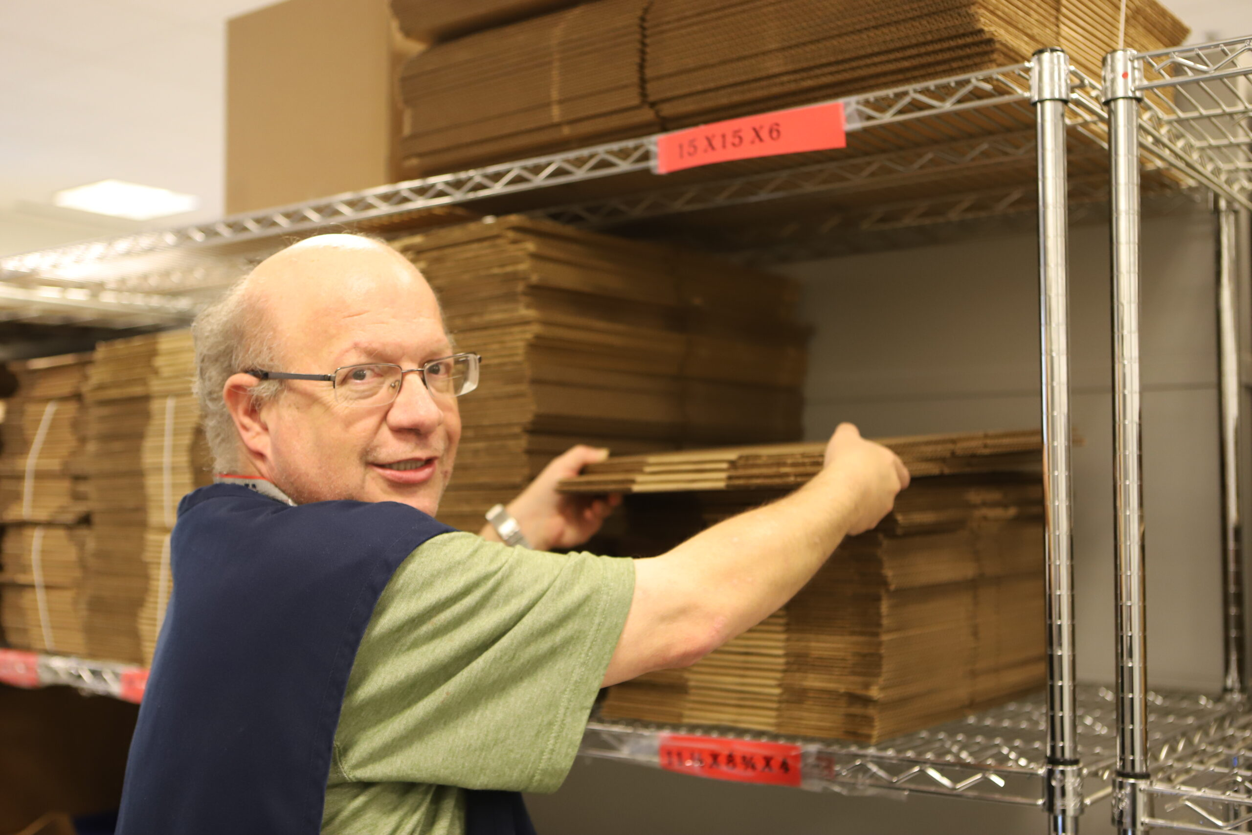 man with hands on cardboard boxes looking at camera