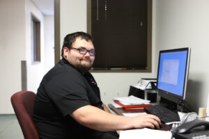 man smiling at camera sitting in front of computer