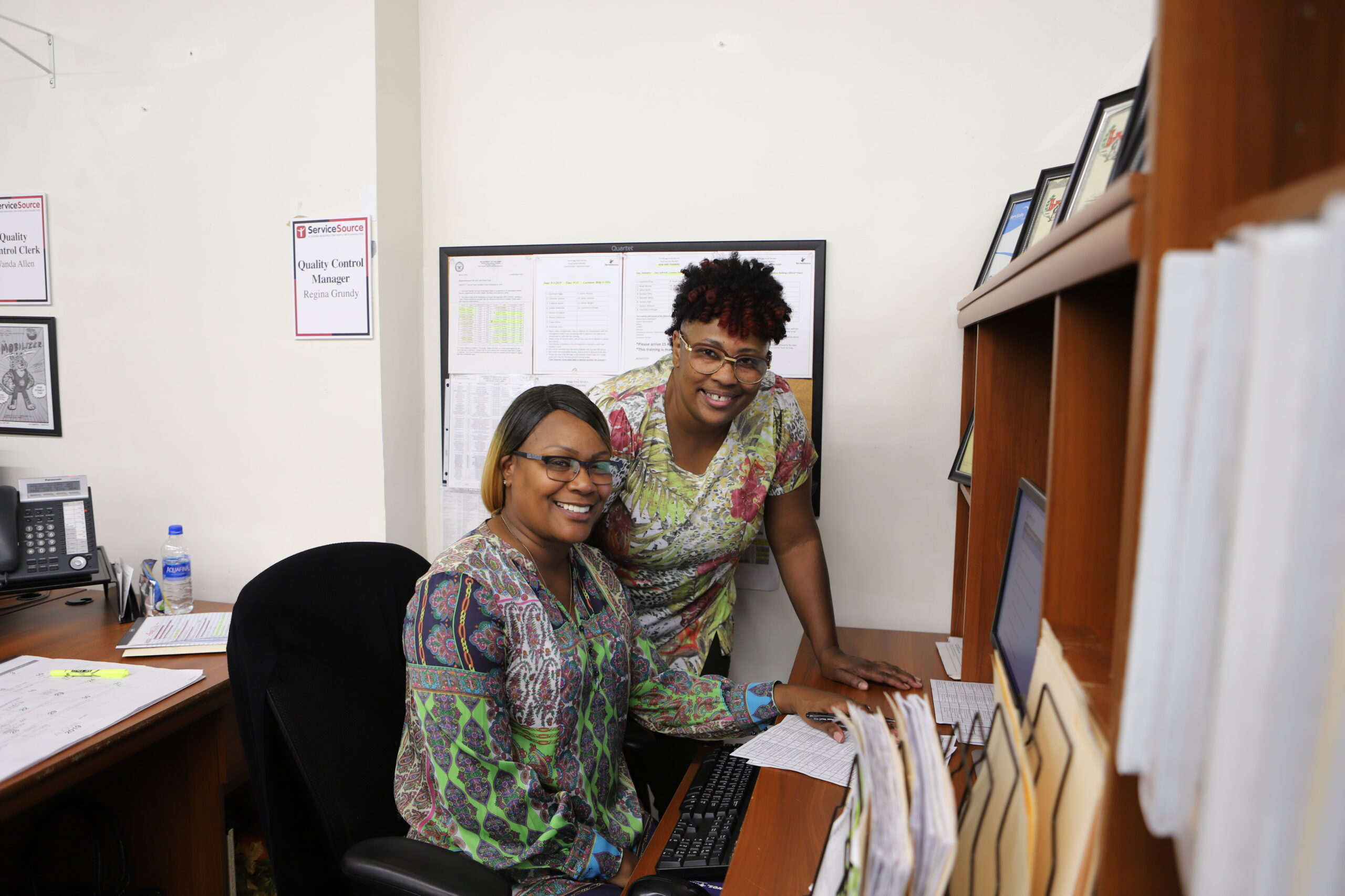 Two women at desk smiling at camera