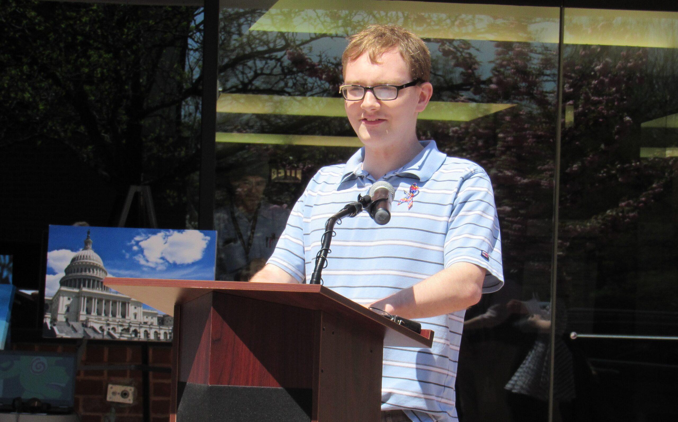 Man at podium speaking into microphone