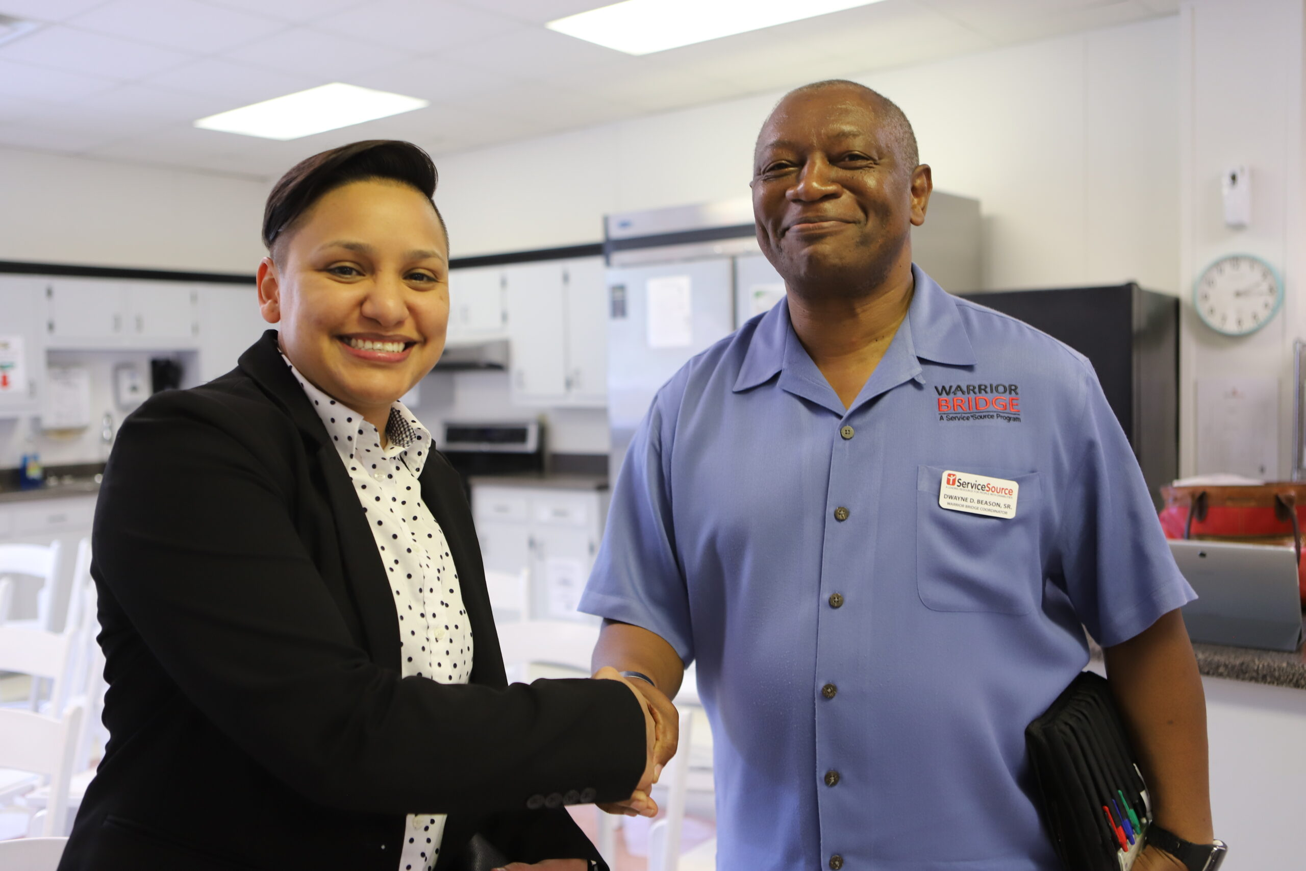 two people smiling at camera shaking hands