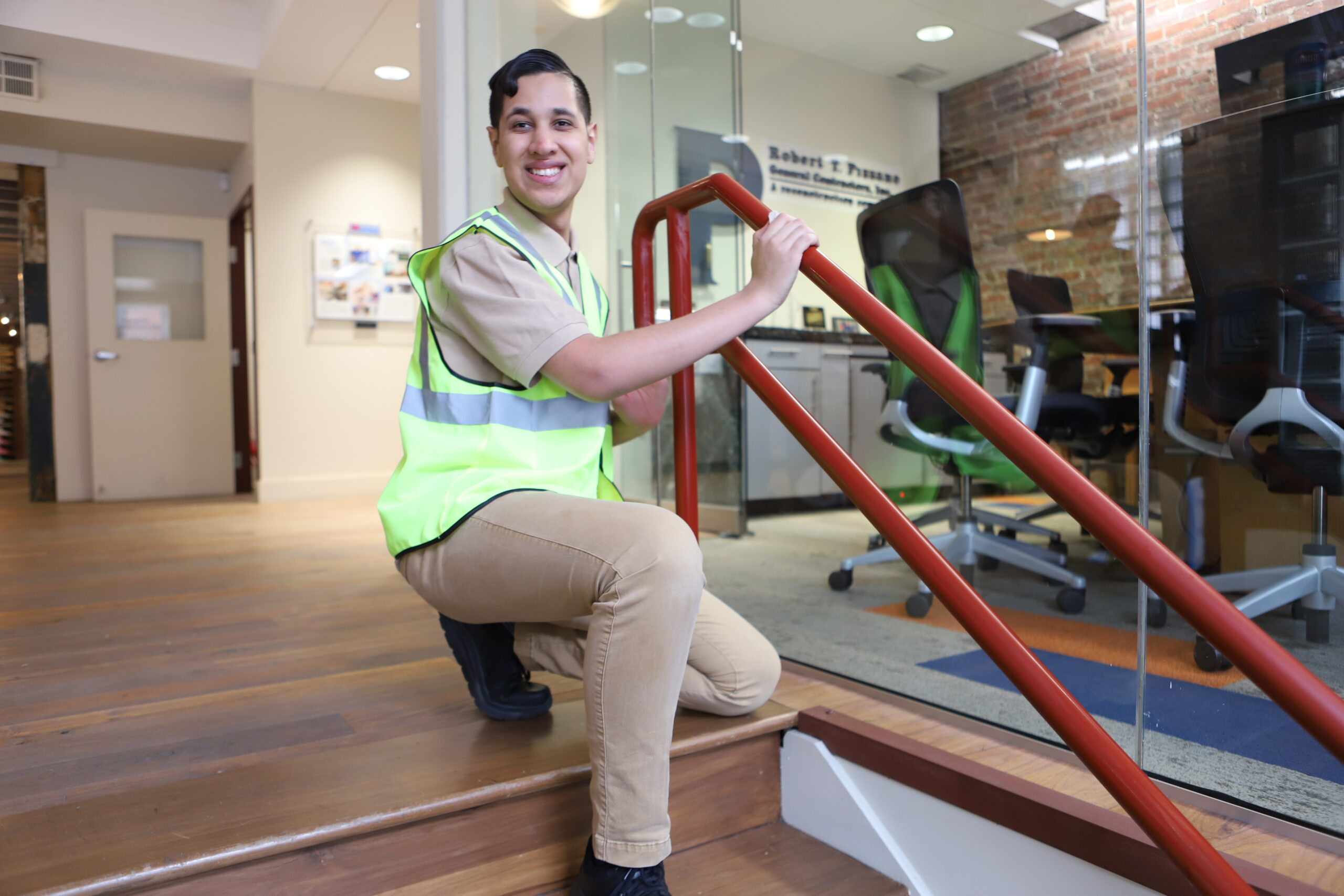 person smiling at camera with hands on stair rail