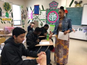 Person standing teaching students at desks