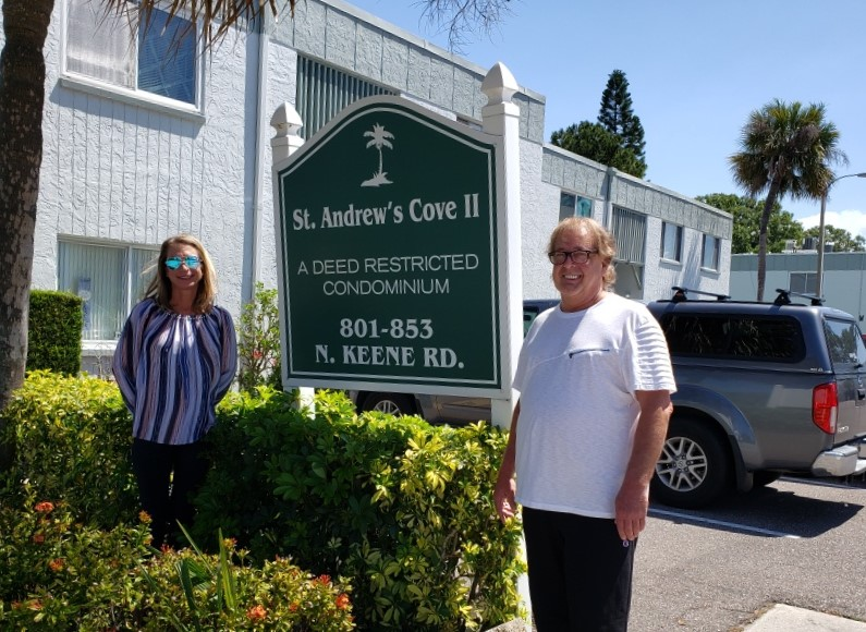 Two people standing outside condo residence in front of sign