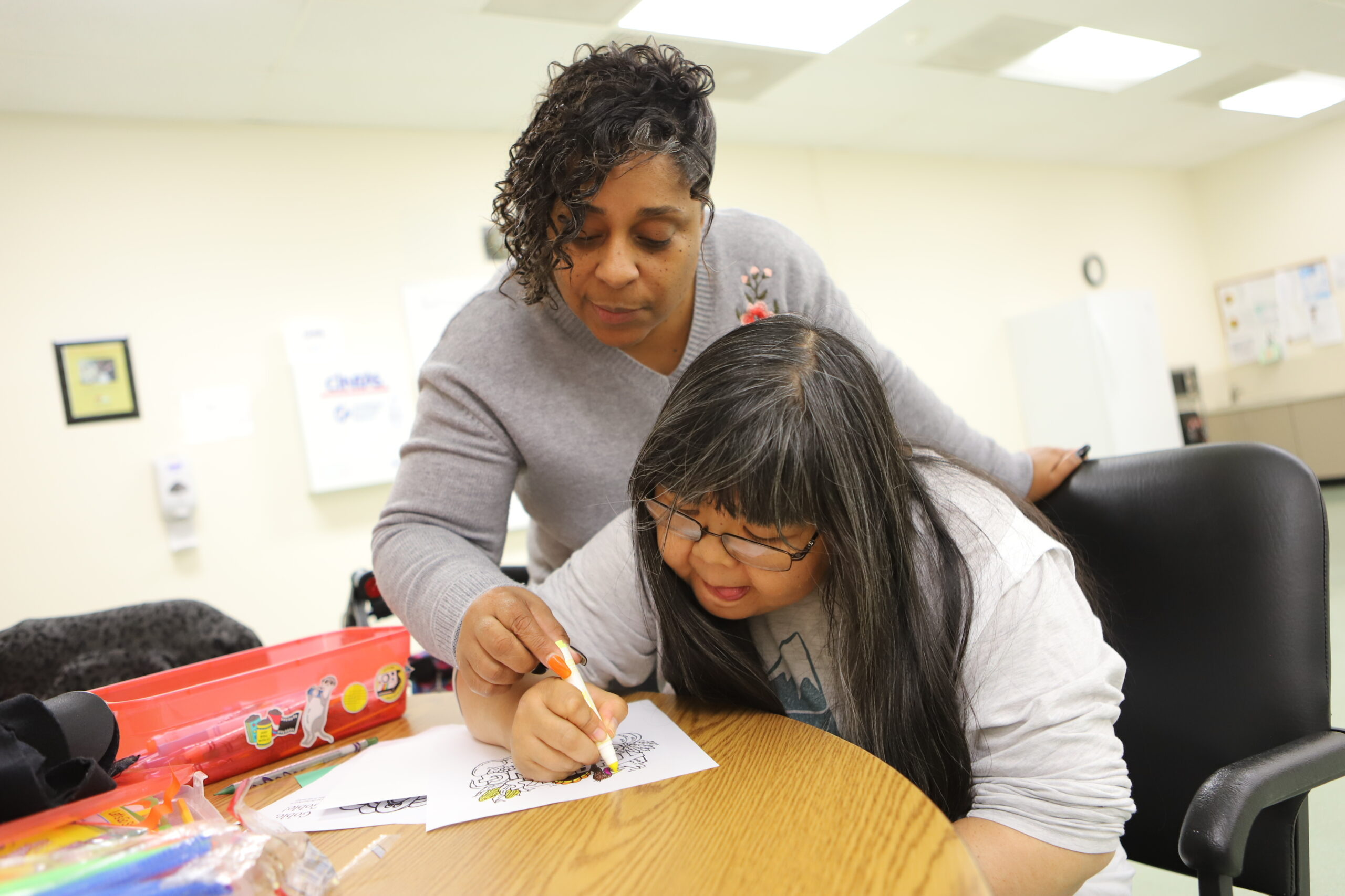 woman looking down helping another person write