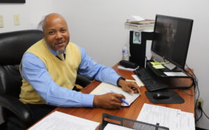man sitting at office desk smiling at camera