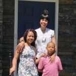 family of three outside front door of house