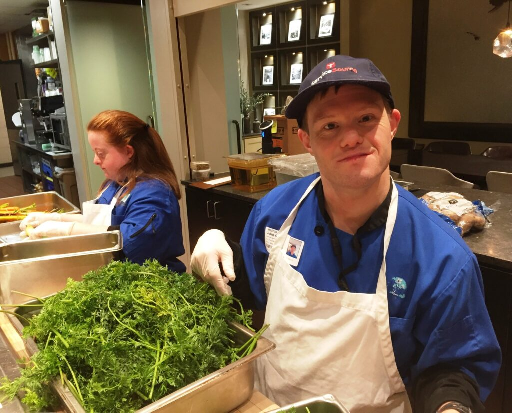 person in kitchen in front of salad greens smiling at camera