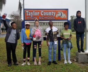 Group of young people standing in front of Taylor County High School sign