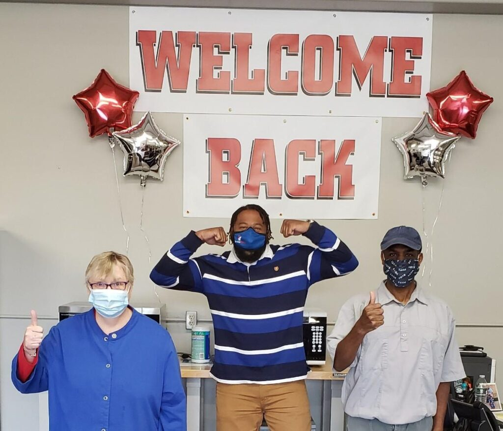 three people in front of welcome sign in masks