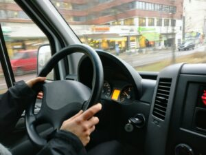 Person with hands on the wheel of car