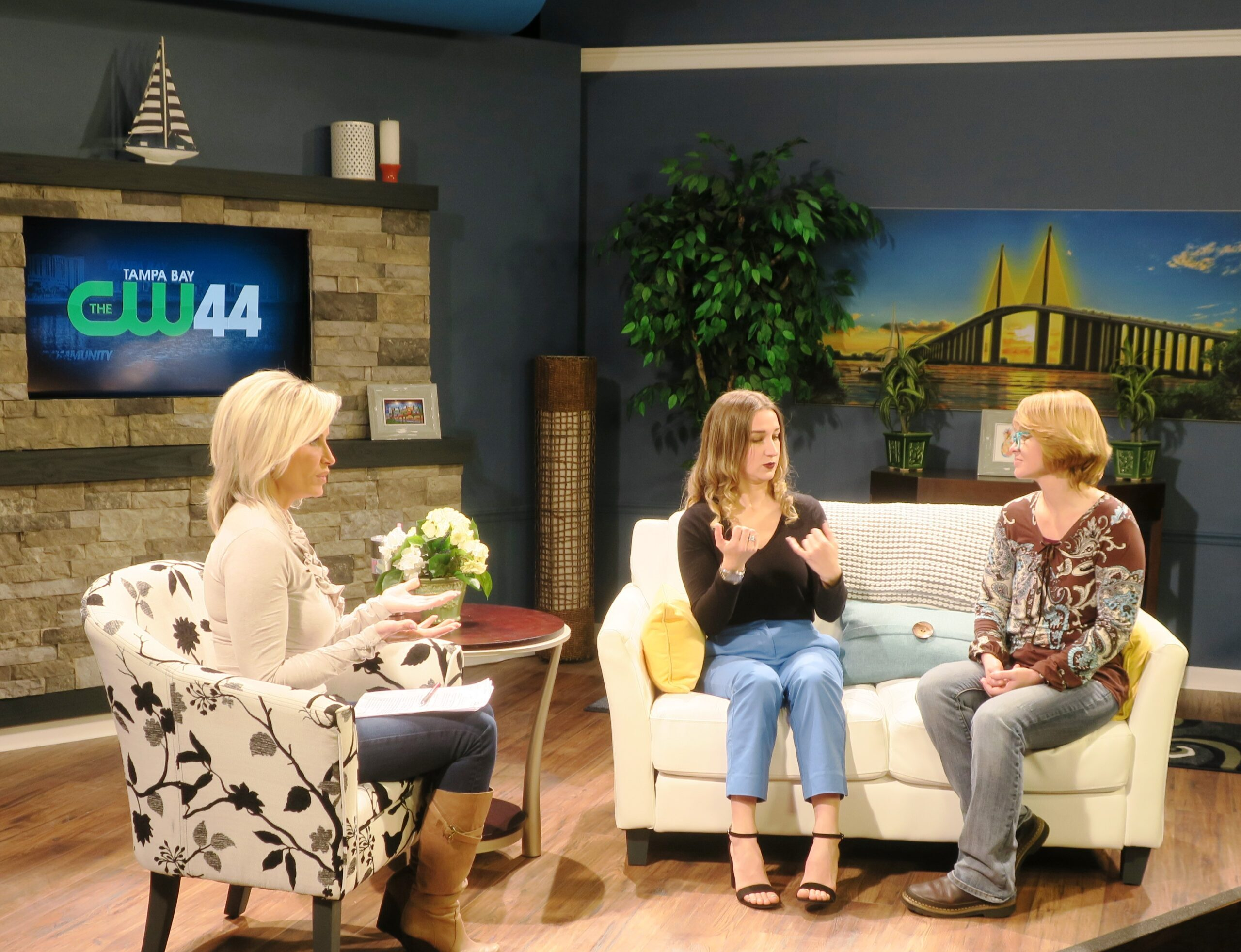 three people sitting on tv set in interview